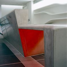 #Concrete reception desk at Canary Wharf under-lit with orange light  #design