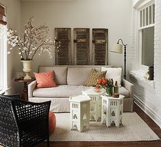 Love this room!  The cluster of Moroccan tables as a coffee table especially.  Not to mention the orange pouf!