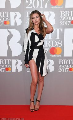 How does she do it? She showed off her model legs wearing a one-shoulder striped deconstructed tuxedo dress which flashed a hint of her bra as she posed for snaps