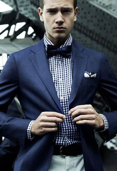 Super chic in a checkered shirt under a navy jacket and bowtie.