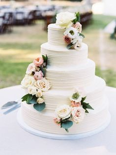Gorgeous summer floral topped cake: http://www.stylemepretty.com/2016/06/23/an-elegant-camp-wedding-complete-with-a-confetti-helicopter-sendoff/ | Photography: Rachel Whyte - http://www.rachel-whyte.com/