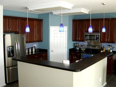 I like the color combo of blue, dark cabinets and countertops with fresh white island and pantry door.  Would totally change the flourescent ceiling lights though