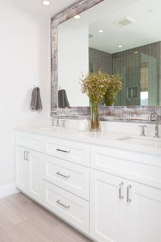 Gorgeous custom vanity with crisp white cabinets and white quartz countertop. Notice the distressed wooden mirror.