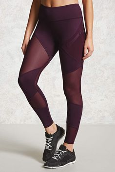 A pair of stretch knit athletic leggings with a sheer mesh insert on each leg, a zipped mesh pocket in front, and moisture management knit.