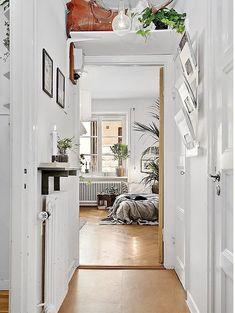 una repisa sobre el radiador, un revistero de pared y una balda volada sobre el marco de la puerta: soluciones para zonas de paso