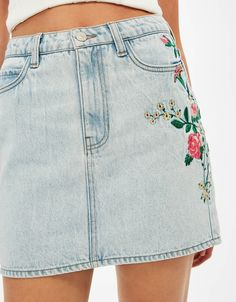 Denim mini skirt with floral embroidery.