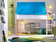 A small kids' bedroom with plenty of space for both sleep and play, with a KLURA loft bed in solid pine and a turquoise KURA bed tent.