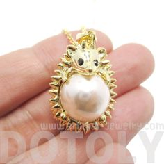 - Details - Sizing An adorable animal inspired necklace featuring a 3D pendant in the shape of a small hedgehog wrapped around a pearl in gold! Store FAQ | Shipping Info | Returns & Exchanges Size: The pendant measures 1.8 cm wide by 2.3 cm tall and hangs on a 16 inch long chain. Material: Gold Plated Brass, Pearl colored bead