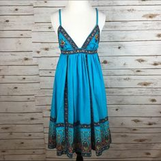 "[Boho Luxe] Floral Babydoll Gypsy Dress Summer Fun Beautiful summer dress in a vibrant turquoise blue. Triangle top with adjustable spaghetti straps. Empire/Babydoll waist with full skirt. Pullover style with keyhole and button closure at back. Trimmed in floral designs embellished with mirrored sequins. Lined. So gorgeous!   Fabric: 100% Cotton  Bust: approximately 14.5"" Waist: 13"" Length: 38"" Condition: EUC. No flaws.  No Trades! Planet Gold Dresses"