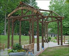 """Bark-on A-Frame Rustic Pergola - A public park playground welcomes young and old alike through a rustic A-frame pergola constructed to follow the """"V"""" shape of the walkway."""