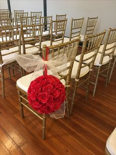 We LOVE how these red roses stand out against the white chairs.