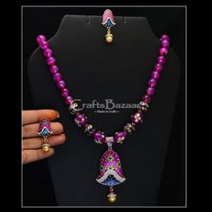 The set comprises of a stunning purple color necklace and exquisite earrings. The pendant of the necklace has a bell shape and displays the ethnic minakari work. The liveliness of the enamel colors is ably matched with a sparking stone set in the pendant itself. The necklace is further embellished with colorful beads as its string which comes with an adjustable option. The earrings also have the same minakari work and have bell shaped beads. #craftsofindia #indianhandicrafts #madeinindia…