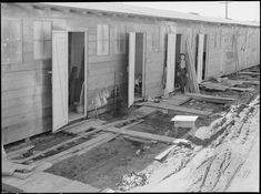 Tanforan Assembly center, San Bruno, California. Barracks for family living quarters. Each door enters into a family unit of two small rooms. Tanforan assembly center was opened two days before the photograph was made. On the first day there had been a heavy rain. When a family has arrived here, first step of evacuation is complete.