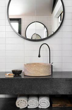 Unique round mirror shaving cabinet, black tap ware. #interiordesign Beecroft House, Sydney