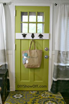 create an organized small entry space with hooks on a door.     {painted horizontal striped curtains}