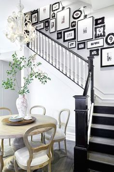 Foyer opens to black and white staircase accented with black and white photo wall alongside an eat-in kitchen boasting light wood round dining table surrounded by wood dining chairs.
