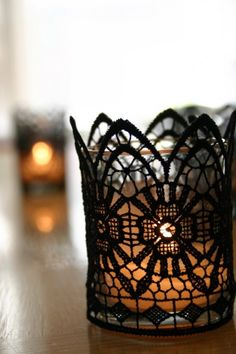 Just pick up a yard or two of black lace trim. Cut off a strip that covers the perimeter of your votive candles. Wrap it around the votive candle and stich to tack in place using black thread.