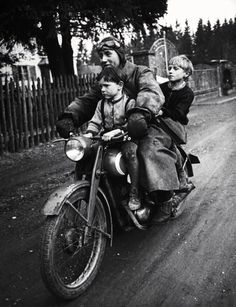A man riding a motorcycle with his two children. Photograph by Walter Sanders. Munich, Germany, May 1949.