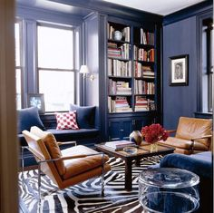 Navy is not a color I would normally think of for a living room, but I absolutely how this is executed, especially with the brown leather chairs.