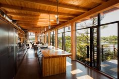 The home maintains remarkable material consistency, with Douglas fir cladding the beams, kitchen countertop, and interior walls. The open-plan kitchen absorbs views of the lake through an expansive glass wall.   Courtesy of CORE Architects.  This originally appeared in Modern Meets Rugged at This Off-the-Grid Retreat in Ontario.