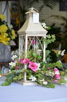 """A delightful silk arrangement in a lantern. Never thought about allowing the flowers to """"spill"""" out of the lantern..."""