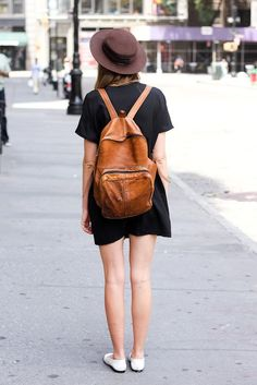 Shop this look on Lookastic:  https://lookastic.com/women/looks/black-shift-dress-white-ballerina-shoes-tobacco-backpack-dark-brown-hat/10552  — Dark Brown Wool Hat  — White Leather Ballerina Shoes  — Tobacco Leather Backpack  — Black Shift Dress