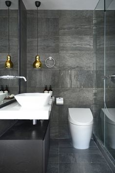 Hewn Gray Marble, Brass Lighting, and Crisp White Porcelain. Masculine Bathroom.