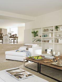 00303899. Chaise longue blanca junto a las mesas de centro del salón y comedor con muebles de madera al fondo de la imagen_00303899