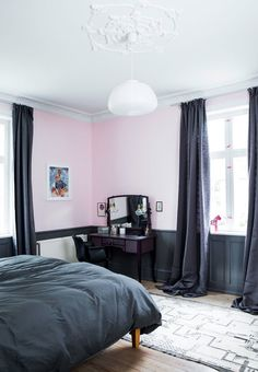 Elegant and feminin master bedroom with pink wall paint color, vintage furniture and floor-length curtains.
