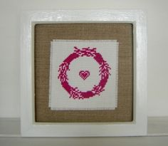 Hand stitched embroidered fuscia pink  floral wreath us. pink wreaths, pink wall decor,hot pink home decor, pink heart wall decor, pink embroiderey, hall decor, White matt painted wood frame which can be hung onto a wall or placed onto a flat surface. Hand stitched cross stitch wreath and heart embroidery which has been mounted onto vintage cotton fabric. Glass cover. Measurements approx 7.5 x 7.5 inches (20cm x 20cm) One of a kind