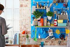 Eine bunte Küche mit Backsteinwand, u. a. eingerichtet mit GRUNDTAL Stangen aus Edelstahl.
