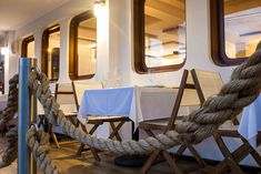 nautical restaurant design, commercial interior design, International Property Awards, wood, rope, brass, chrome, boat, yacht, vintage, antiques, lamp, stucco wall, wall paper, woven material by sara battelli photo by elenathani