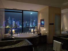 Bathroom with lit candles and a city view
