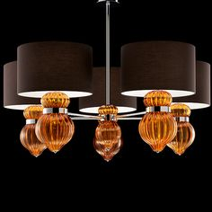 Barovier & Toso - A shapely collection with Boteroesque contours and generous dimensions. The two suspension chandeliers have a diameter of 120 cm (3-light) and 150 cm (5-light) with oversized lampshades, and can be matched with wall lamps of two different dimensions. The family is rounded out by two desk lamps, both of which are also in two size variations. The chromed neck is typical of the entire line.