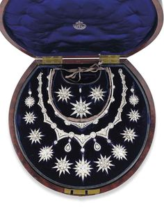 Victorian diamond star parure, c1870, mounted in silver and gold and comprising a tiara, necklace and ear pendants. The tiara is set with six graduated old-cut diamond flowerhead clusters with old-cut diamond collets and triangular intersections, surmounted by nine detachable star motifs. The necklace is of similar design, with five detachable star motifs. In a fitted wooded case with various fittings for brooch and pendant conversion