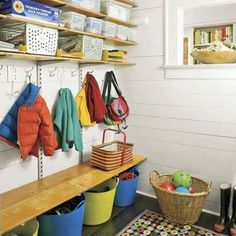 Love the colorful buckets and wooden bench in this mud room. #getorganized