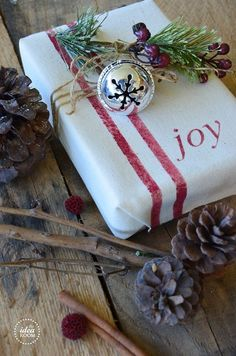 silver jingle bells and simple fabric printed with Christmas message -- gift wrap by Ana Rosa