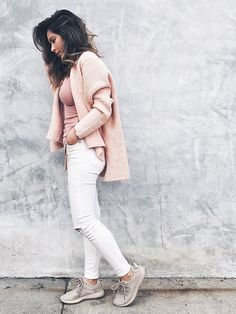 Marianna Hewitt wears a pink top, sweater, skinny jeans, and Yeezy Boost sneakers