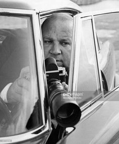 The famous private detective Tom Ponzi taken into a car with the door half open; in his hands he holds his camera with a large telephoto ready to shoot. Milan (Italy), July 1963