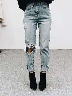 Trendy distressed denim blue jeans with black boots.