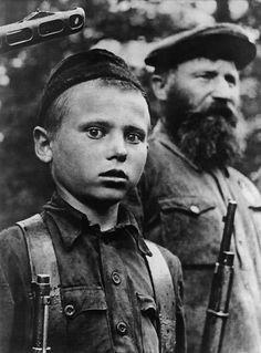 1. Deze foto is ergens in een oorlog gemaakt. Je ziet een jongetje die recht in de camera kijkt.  2. De foto is erg sterk door de gezichtsuitdrukking van de jongen. Hij kijkt heel bang en zenuwachtig. De man naast hem is juist erg rustig. Ook hebben ze allebei een geweer vast, terwijl de jongen nog erg jong is. Ook zie je een geweer boven het hoofd van de jongen. De foto is zwart wit wat de sfeer van de foto nog zwaarder en heftiger maakt