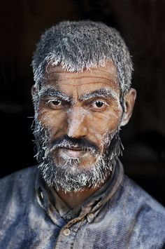 Man coated in sugar in a candy factor in Kabul, Afghanistan.