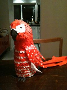 Sinterklaas surprise, altijd weer leuk om te maken! Papegaai van lege fles siroop, papier maché en kleine stukjes papier in wit en rood.
