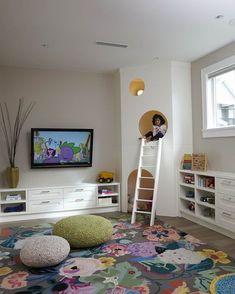 Particolare stanza per bambini con una piccola casa di gioco posizionata in un angolo. Anche il tappeto multicolore offre un tocco di allegria