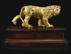 North Italian, probably Venice, late 16th/ early 17th century PACING LION gilt bronze, on a wood base bronze: 8 by 17cm., 3 1/8  by 6 5/8 in.