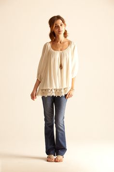 Long white boat-necked peasant blouse with thick (crocheted?) embellishment on hem.  The shirt & the sandals are both great.  Casual & comfy - perfect summer-wear!