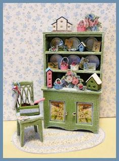 """1/4"""" Mayblossom Morning Kit - Kit includes: Hutch, chair, rug, May Day baskets & tussie mussie, seed packets & soil, seed crate & trowel, birdhouses, accessories, artwork and instructions. Finished Size: Hutch approx 1"""" w x 1 3/4"""" h. Chair approx 1/2"""" w x 1"""" h"""