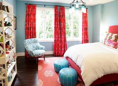Turquoise blue & red teen girl's bedroom with turquoise blue walls paint color, red curtains window panels, red upholstered bed, Madeline Weinrib Atelier Red Mandala Rug, turquoise blue Moroccan leather poufs, blue glass bottles chandelier.
