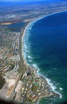 """Bloubergstrand from the air. Bloubergstrand is a suburb of Cape Town along the shores of Table Bay, about 25 km to the north of the city centre of Cape Town. The name Bloubergstrand literally means """"blue mountain beach"""" in Afrikaans. Paises Da Africa, Namibia, Cape Town South Africa, Wale, Africa Travel, Countries Of The World, Aerial View, Places To See, Beautiful Places"""
