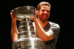 Corey Crawford smiles for a photo with the Stanley Cup.
